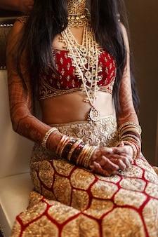 Indische braut im wunderschönen roten kostüm sitzt auf dem weißen stuhl