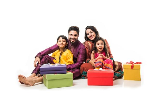 Indische familie feiert diwali oder deepavali in traditioneller kleidung beim sitzen isoliert auf weißem hintergrund mit geschenkboxen und lampe in thali