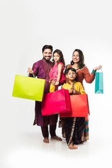 Indische familie feiert diwali oder deepavali in traditioneller kleidung mit einkaufstüten, isoliert auf weißem hintergrund