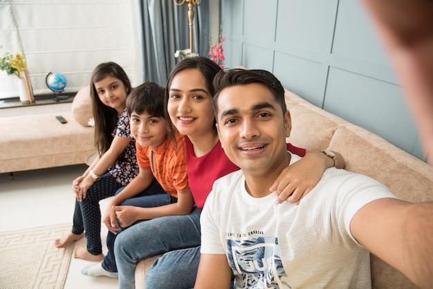 Indische familie sitzt auf dem sofa und macht ein selfie-foto mit dem smartphone