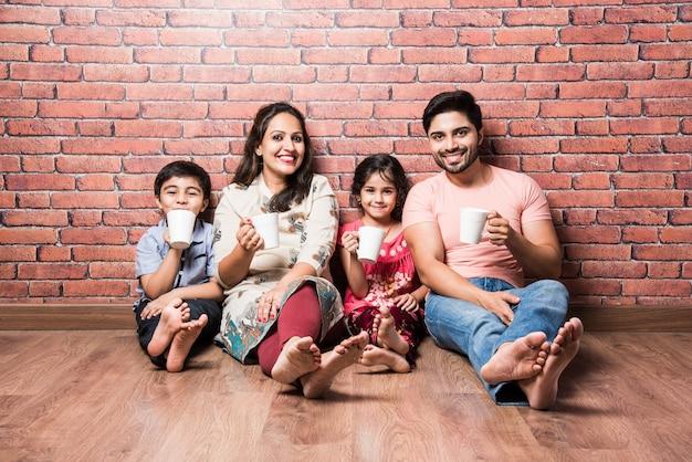Indische familie trinkt milch weiß auf holzboden gegen rote backsteinmauer drinnen sitzen