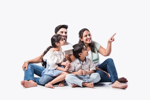 Indische familie vater, mutter, sohn und tochter mit 3d-papiermodell des hauses - real estate concept in indien