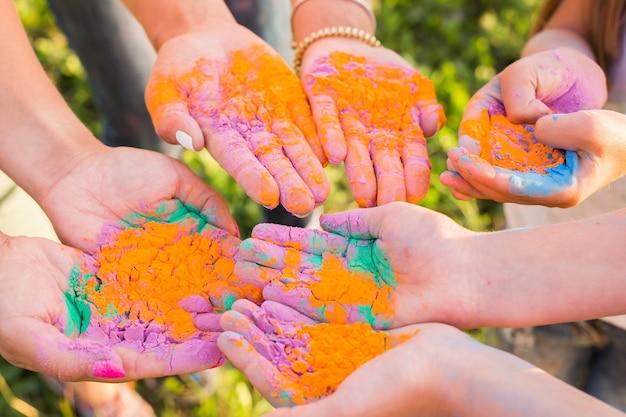 Indische feiertage, spaß, fest des holi und menschenkonzept - weibliche hände mit mehrfarbigem pulver auf fest des holi