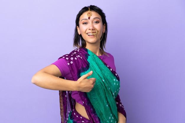 Indische frau auf lila wand, die eine daumen hoch geste gibt