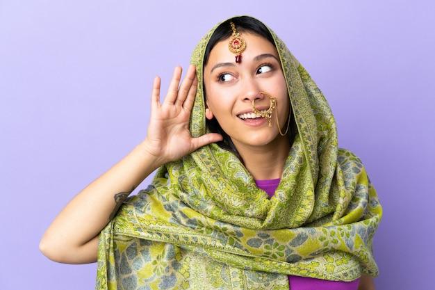Indische frau auf lila wand, die etwas hört, indem man hand auf das ohr legt