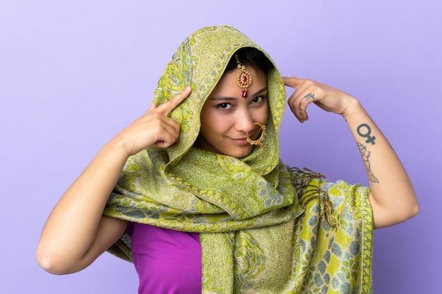 Indische frau auf lila wand, die zweifel und denken hat