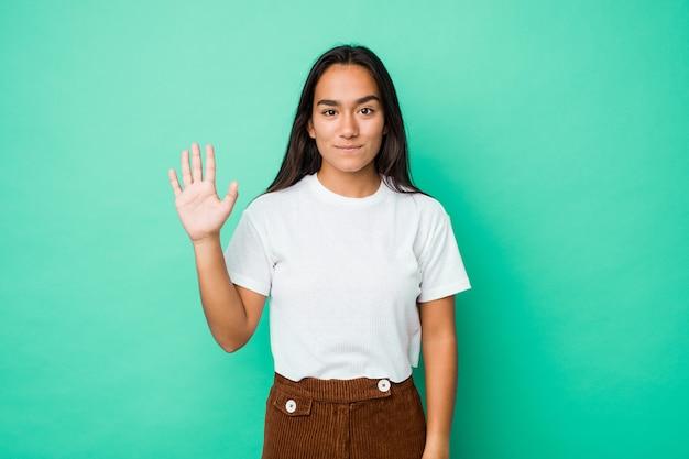 Indische frau der jungen mischrasse lokalisierte die lächelnde nette vertretung nr. fünf mit den fingern.