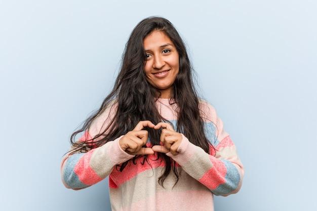 Indische frau der jungen mode, die eine herzform mit ihm hände lächelt und zeigt.