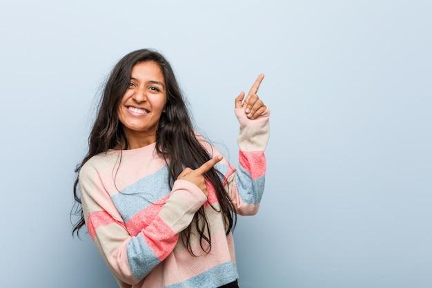 Indische frau der jungen mode, die mit den zeigefingern auf einen kopienraum zeigt, aufregung und wunsch ausdrückt.