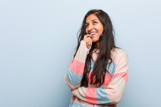 Indische frau der jungen mode entspannte sich das denken an etwas, das einen kopienraum betrachtet.