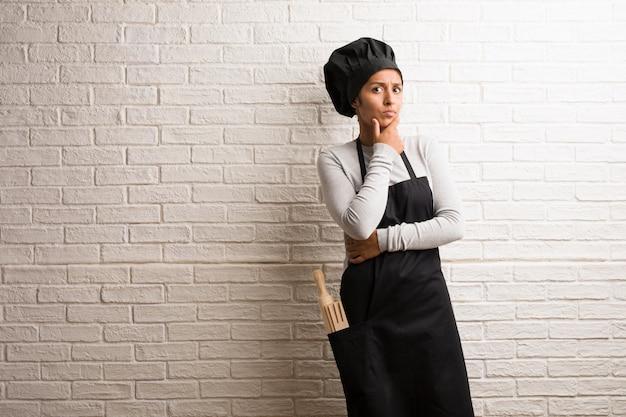Indische frau des jungen bäckers gegen eine ziegelsteinwand oben denkend und schauend