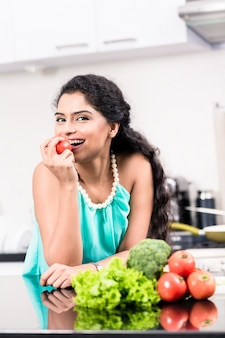 Indische frau, die gesunden apfel in ihrer küche isst