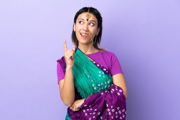 Indische frau isoliert auf lila denken eine idee, die den finger nach oben zeigt
