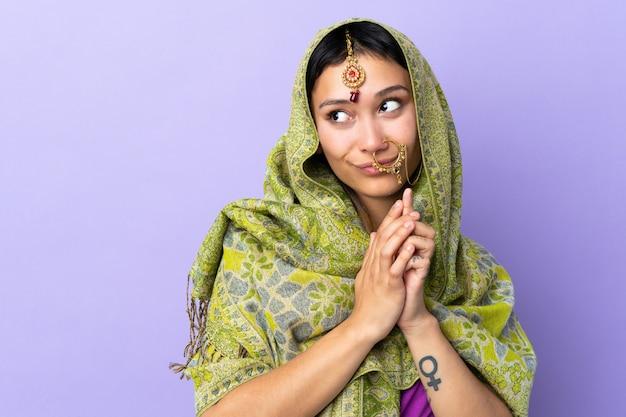 Indische frau isoliert auf lila wand, die etwas entwirft