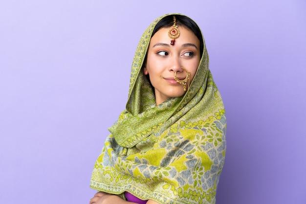 Indische frau isoliert auf lila wand mit verschränkten armen und glücklich