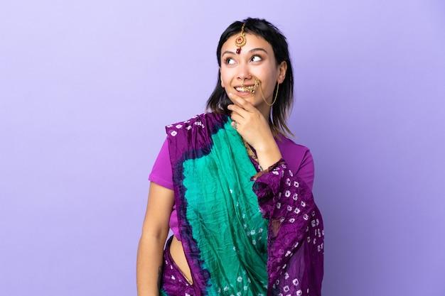 Indische frau lokalisiert auf lila wand, die beim lächeln nach oben schaut