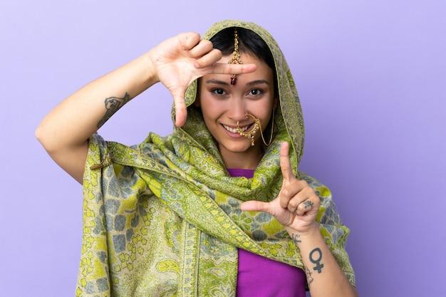 Indische frau lokalisiert auf lila wand, die gesicht fokussiert. rahmensymbol