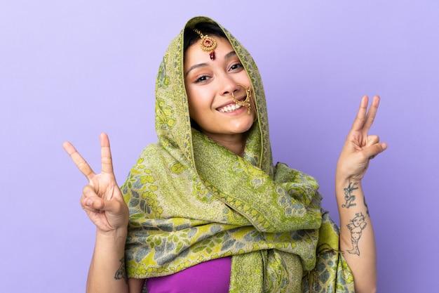 Indische frau lokalisiert auf lila wand, die siegeszeichen mit beiden händen zeigt