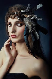 Indische frau mit federn im haar, porträt der indianischen mädchenschönheit auf dunklem hintergrund im rauch. schönes gesicht mit sauberer haut, kontrastierendes make-up