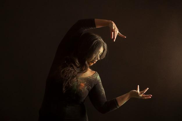 Indische frau tanzt zu holi-musik, die mit farbigem staub bedeckt ist