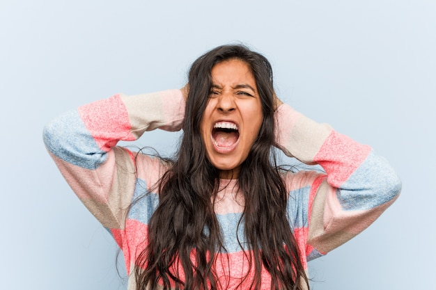 Indische frauenbedeckungsohren der jungen mode mit den händen, die versuchen, nicht zu lauten ton zu hören.