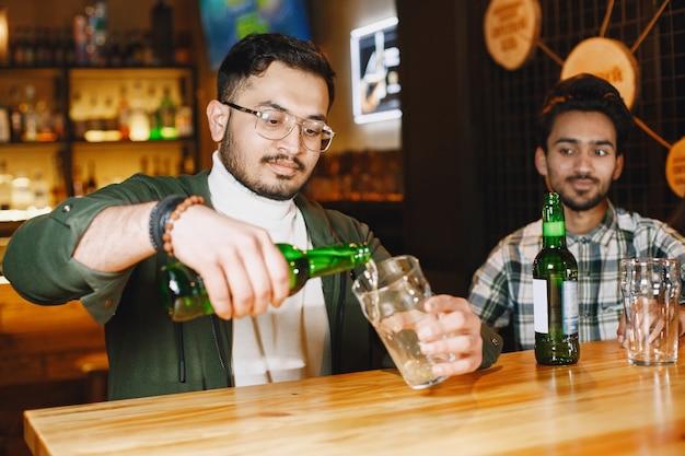 Indische freunde in einer kneipe. jungs und mädchen an der bar. feier bei einem krug bier.