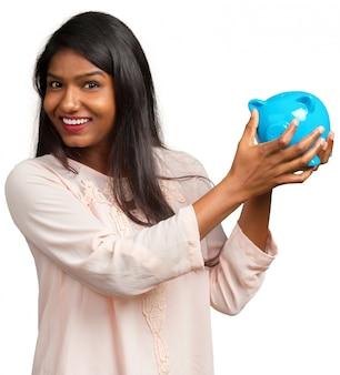 Indische geschäftsfrau, die geldsparschwein spart