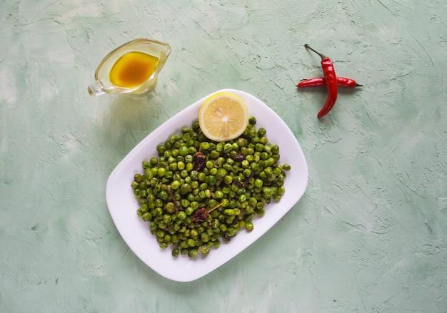 Indische gewürzerbsen. traditioneller inder schmücken von gebratenen grünen erbsen mit gewürzen.