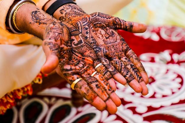 Indische hochzeitszeremonie: bräutigamhand mit mehandi-design