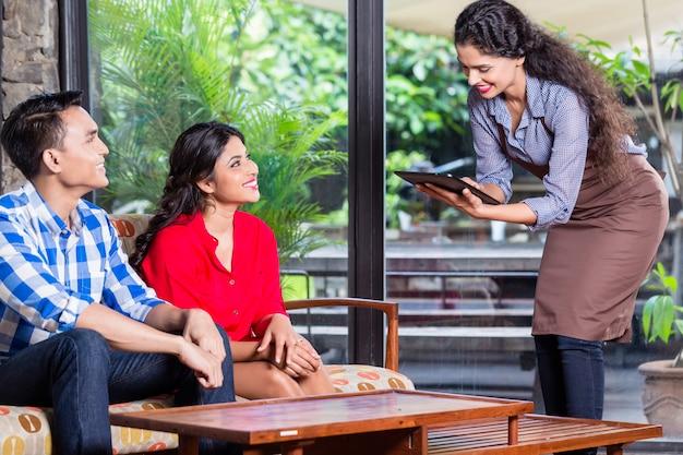Indische kellnerin, die bestellungen im café oder im restaurant entgegennimmt