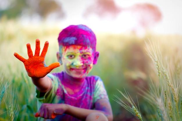 Indische kinder, die mit der farbe in holi festival spielen