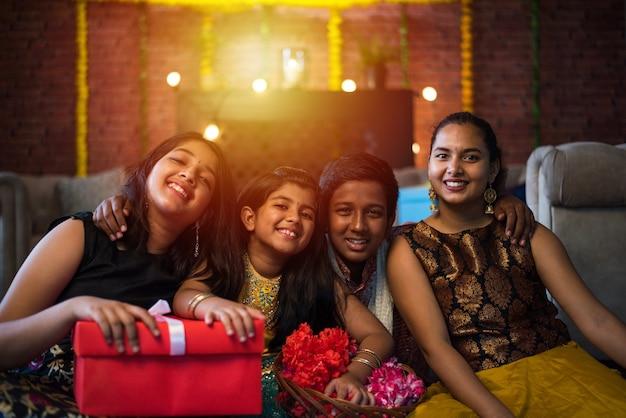 Indische kinder feiern diwali, deepawali, bhai dooj oder rakhi oder raksha bandhan mit blumenrangoli, geschenken, diya