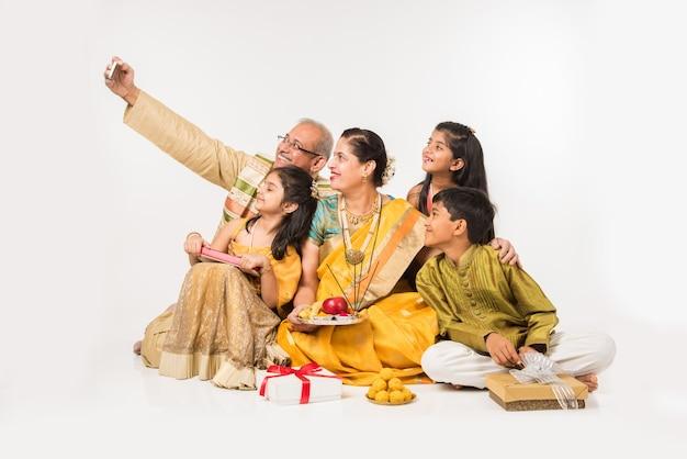 Indische kinder mit großeltern in traditioneller kleidung, die geschenke, süßigkeiten und puja oder pooja thali halten oder selfie machen, einzeln auf weißem hintergrund