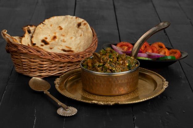 Indische küche bhindi masala auf holzoberfläche