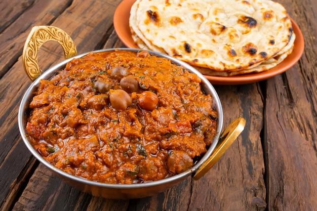 Indische küche chana masala diente mit tandoori roti auf hölzernem hintergrund