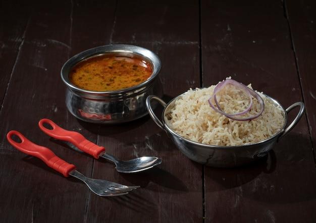 Indische küche jeera reis mit dal tadka auf hölzernem hintergrund