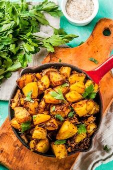 Indische lebensmittel bombay-kartoffeln auf hellblauem hintergrund