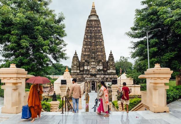 Indische leute, die barfuß zum mahabodhi-tempel für das beten und den pilger beim regnen bei bodh gaya, bihar, indien gehen