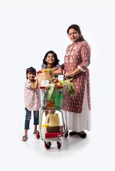 Indische mutter und tochter mit einkaufswagen oder trolley isoliert über weißer wand