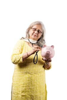 Indische oder asiatische ärztin in uniform mit stethoskop, die apfelfrüchte hält oder beats im sparschwein überprüft