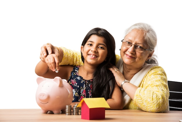 Indische oder asiatische oma, die der süßen enkelin die bedeutung des sparens beibringt und münzen in das rosa sparschwein steckt
