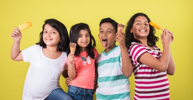Indische oder asiatische süße kleine kinder, die eiscreme oder mangoriegel oder süßigkeiten essen. auf buntem hintergrund isoliert