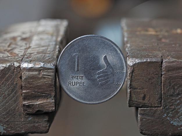 Indische rupienmünze in einem metallschraubstock auf beiden seiten festgeklemmt