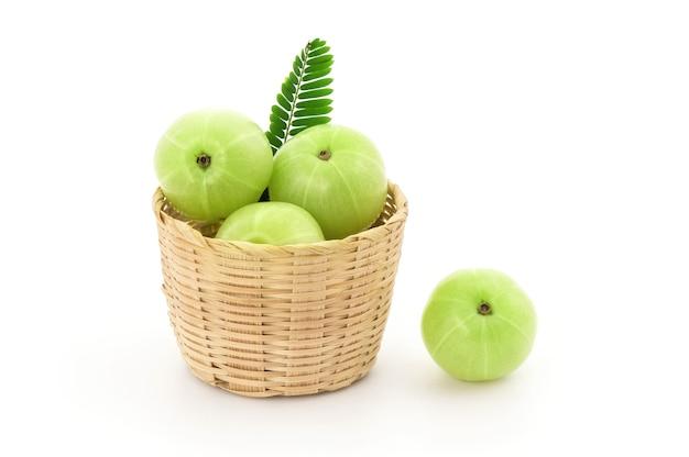 Indische stachelbeer- oder phyllanthus emblica-früchte und grüne blätter lokalisiert auf weiß mit beschneidungspfad.