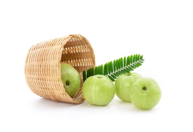 Indische stachelbeer- oder phyllanthus emblica-früchte und grüne blätter lokalisiert auf weiß.