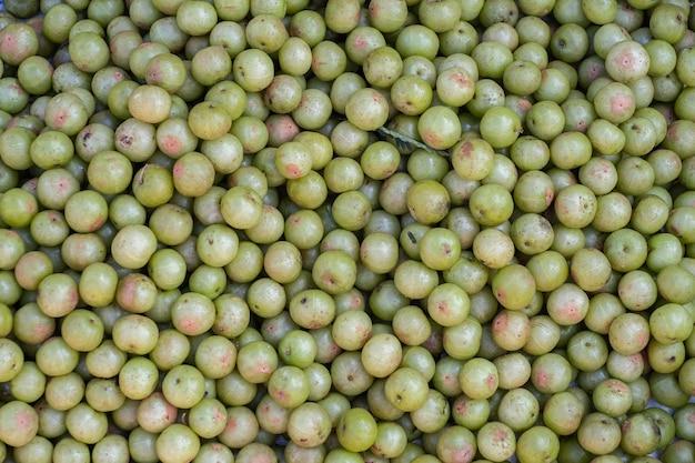 Indische stachelbeere (phyllanthus emblica), malakka-baum oder amla-frucht. emblic früchte zum verkauf auf dem markt.