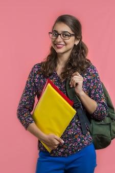 Indische studentin in den gläsern mit ordnern und büchern
