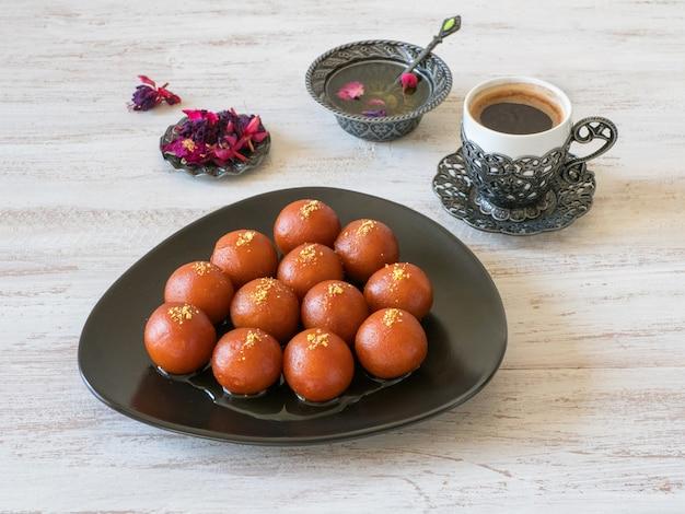 Indische süßigkeiten. traditioneller süßer gulab jamun auf einem weißen holztisch.
