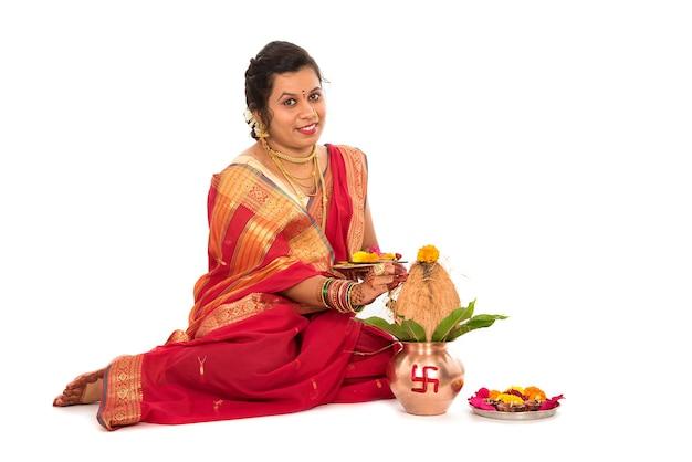 Indische traditionelle frau, die anbetung mit kupferkalash durchführt