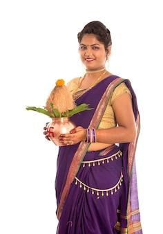 Indische traditionelle frau, die eine traditionelle kupferkalash hält